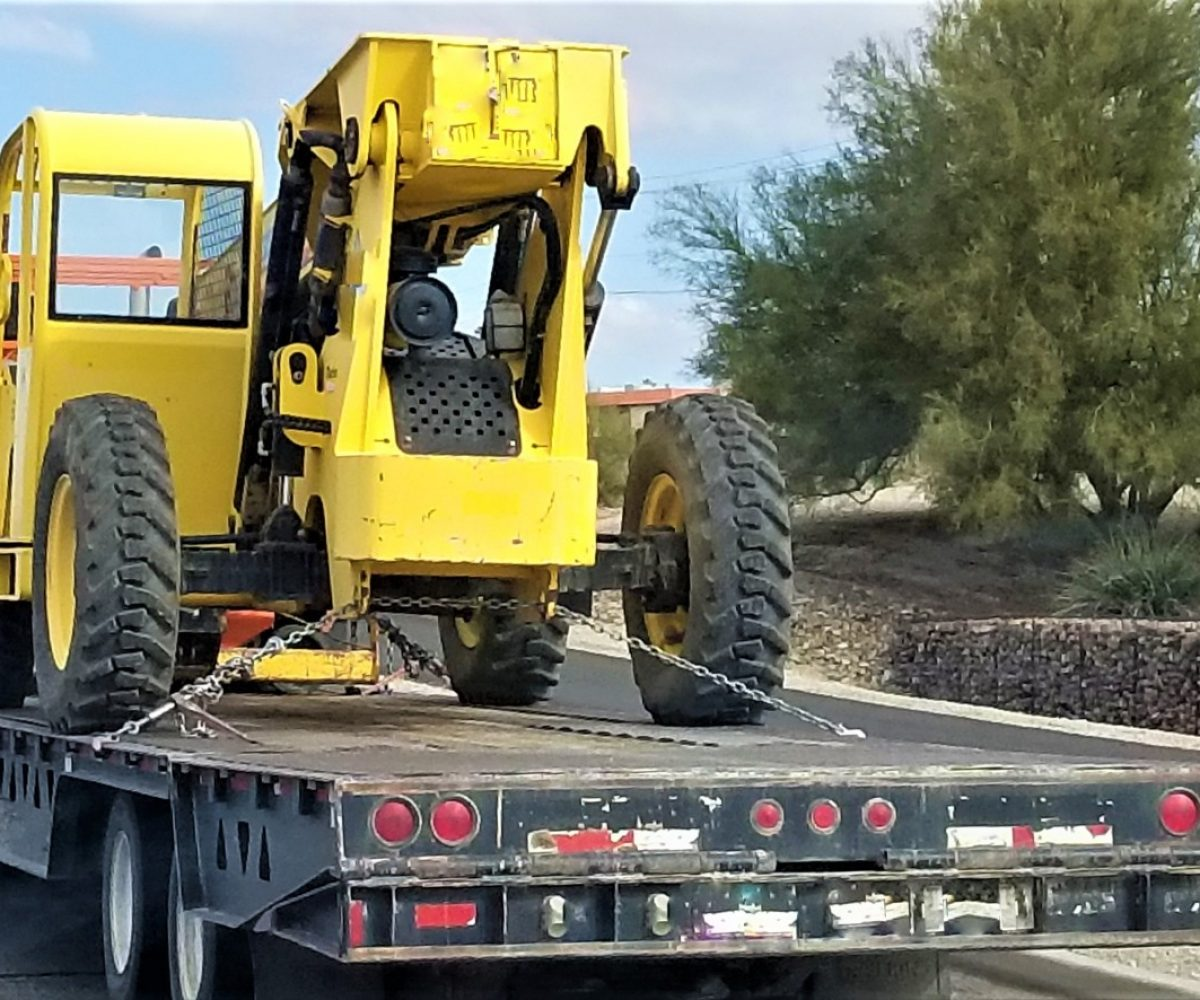 transportation-and-logistics-a-big-rig-semi-truck-towing-a-low-boy-trailer-with-a-big-yellow-bucket_t20_nLvpN6